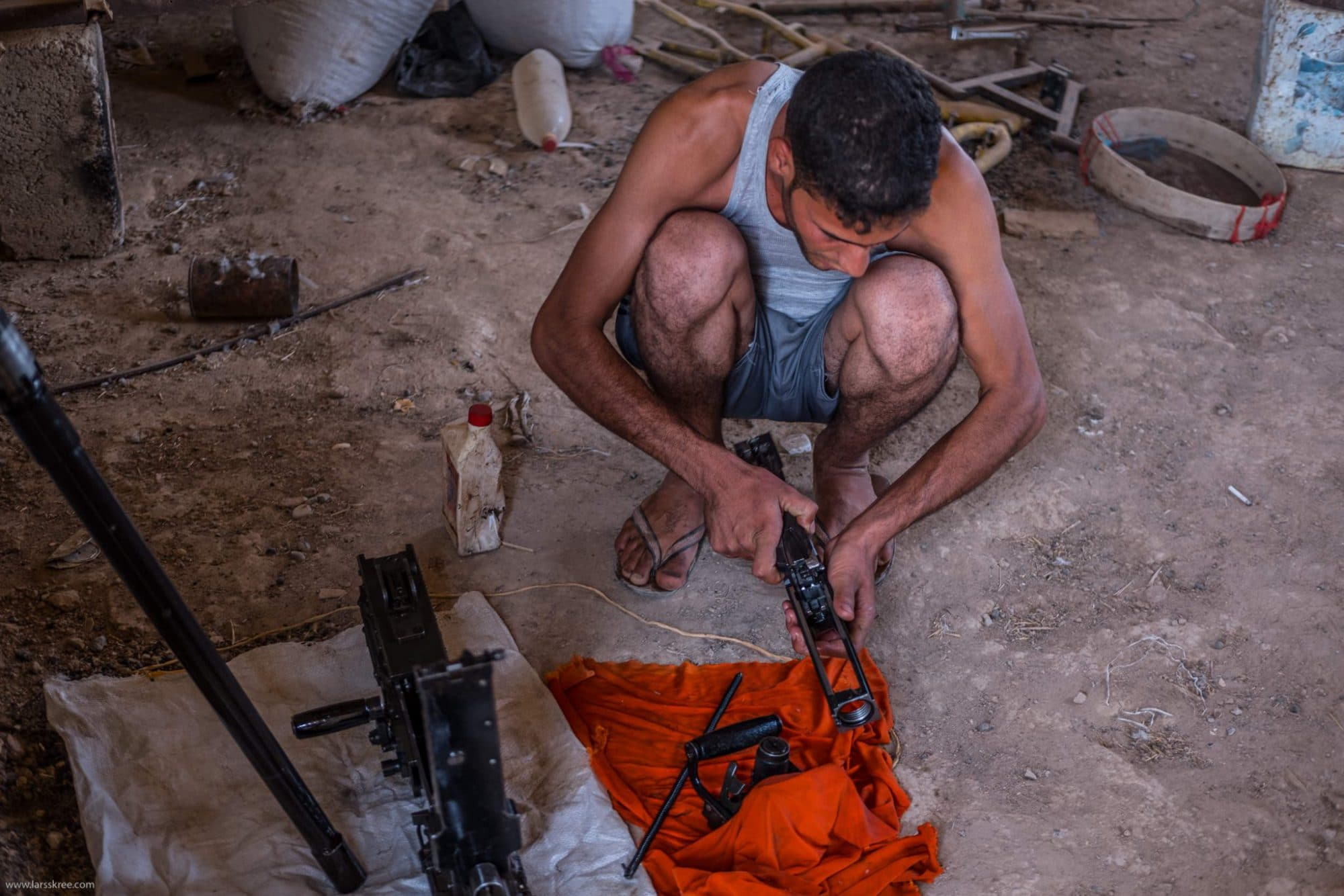 Guy from local shia militia cleaning his weapon